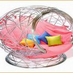 ultra modern bedroom comfy chair design with sophisticated stainless steel net cage and pink bolster and colorful cushions