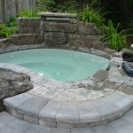 unique and natural built in hot tub design with concrete stone deck and small garden landscape with shady tree