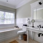 white bathroom idea with white bathtub and vanity with rectangle wall mirror and patterned flooring with storage