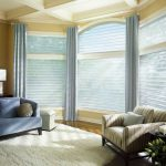 window coverings for bay windows with blue curtain and blinds in living room woth blue sofa and striped armchair plus soft rug and wooden side table