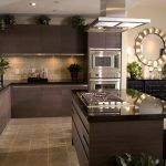 Wonderful Kitchen Design With Brown Cabinetry With Round Framed Wall Mirror With Island And White Seating Aside Dining Table