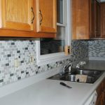 wonderful kitchen design with wooden cbainetry and groutless backsplash idea with white countertop and modern stain sink