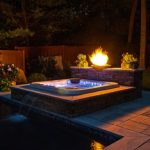 wonderful view of outdoor built in hot tub design with pave patio deck and fire pit and greenery