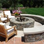 wooden armchair design with white bolster with stone in ground fire pit with reddish patio design aside grassy meadow