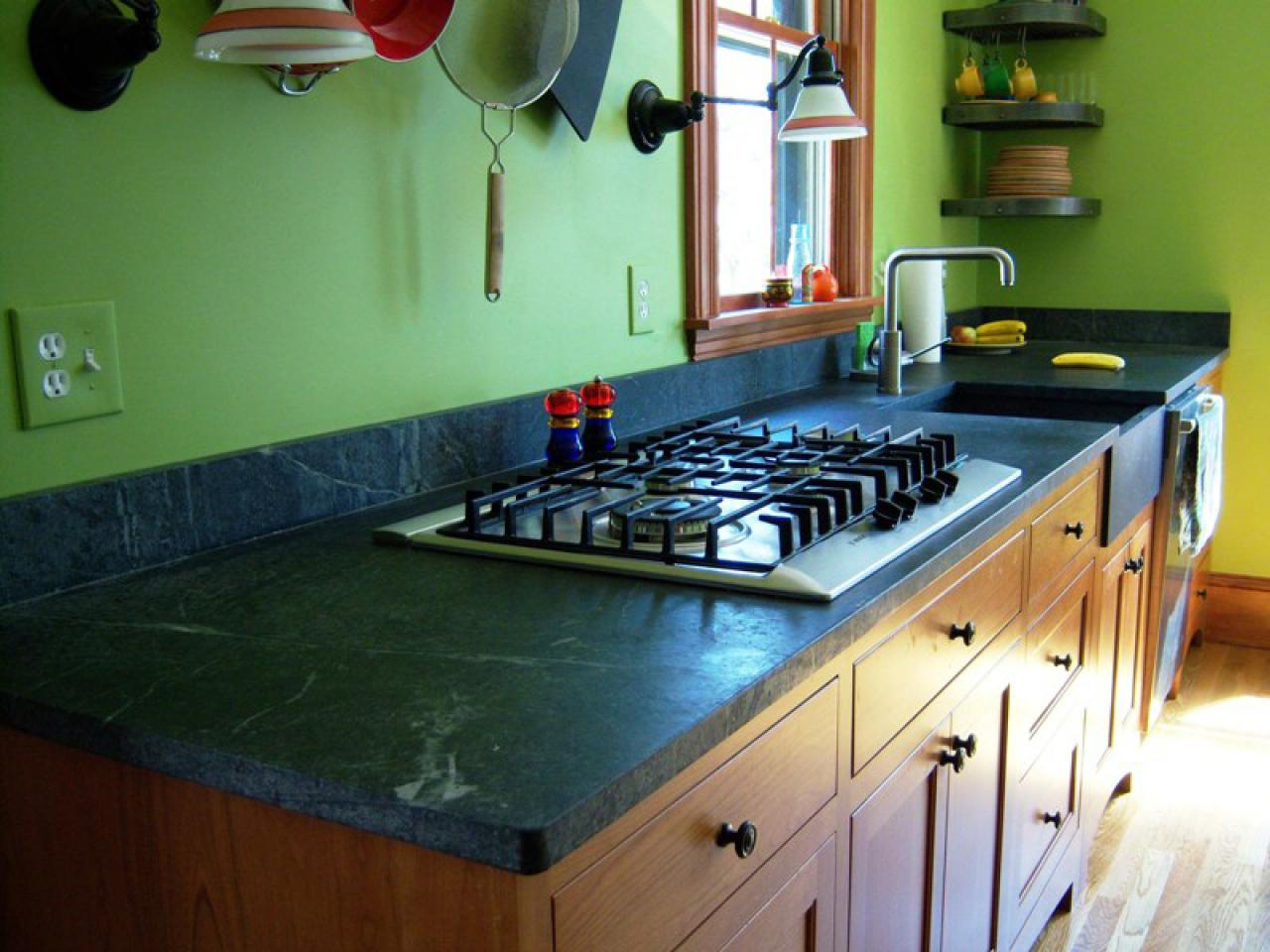 wooden cabinet with black soapstone countertop with modern cooktop beneath green wall design with wall racks