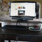 wooden monitor stand ikea on black wooden office desk with drawer underneath plus keyboard and mouse decorated in bedroom