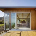 zero energy home with full wood structure and large glass door and windows