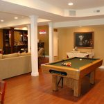 A billiard table yard with hardwood structure an entertainment corner a console table with painting on wall and wood planks floor for basement