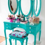 A classic vanity with small drawers chair without backrest three side decorative mirrors