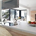 A kitchen island with white counter plus electric stove and storage in wood material a fresh fruits some electric kitchen appliances large glass windows for kitchen room