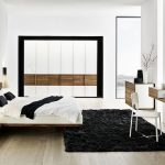 A modern bedroom with black wool area rug a modern vanity integrated with frameless mirror a white chair wooden drawer system lof bed with headboard plus bedside table modern wall lamps