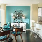 An open space for modern kitchen with kitchen bar and also dining room two barstools a set of dining furniture a white credenza with twin table lamps a beautiful wall decoration turquoise wall paint