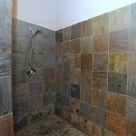 Artistic walk in shower space no door with stainless steel heldhand showerhead natural tone color tiles for wall and floor system