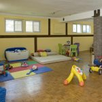 Basement 's interior design as the playground with a lot of kids' toys and furniture for kids