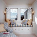Bay windows bench with storage comfy pillows relaxing and reclining chair a pair of double wall sconce light fixtures white area rug