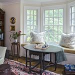 Bay windows with bench and pillows round table area rug wood floors book rack a console table