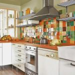 Beautiful backsplash in multicolors orange kitchen counter white painted cabinets electric stove metal floating shelves for organizing cooking tools and dishware collections
