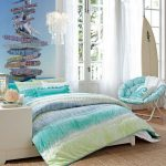 Beautiful beach  bedroom idea with a decorative chair in blue and white colors gradation colored bedcover and pillow covers unique wallpaper a bedside table integrated with bed furniture