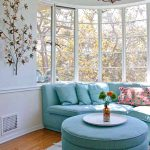 Beautiful curved sofa with blue pillows and blue ottoman table as bay window furniture small sized white area rug wood floors beautiful wall art classic pendant chandelier