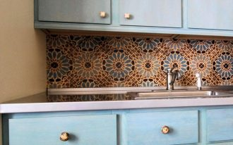 Beautiful kitchen backsplash in multicolor and flower patterns a kitchen sink and faucet blue kitchen cabinetry and base drawer system