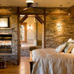 Bedroom Decorating Idea In Rustic A Wood Bed Furniture With Crafted Wood Headboard Bricks Wall System Two Sided Fireplace A Chair And Round Table In Rustic Look A Ceiling Fan With Lighting
