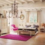Bedroom rug in pink wood planks floors rustic bed furniture with headboard a pink reading chair a pair of rustic bedside tables with table lamps a decorative mirror a classic pendant chandelier