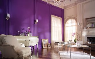 Bold purple paint for wall a pair of wall sconces lamps a classic console table in white a classic corner chair with white pillow a small settee a fireplace beautiful crystal pendant lamp white wool rug