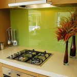 Bright and gloss green kitchen backsplash two decorative glass vases with decorative plants mini gas stove spoons and forks hanger made of stainless steel two small containers made of stainless steel