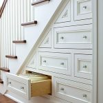 Built in drawer system under the stairway in modern style wood planks flooring system