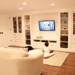 Built in shelves unit for organizing and displaying book collections ornaments and box storage in basement white rug wood floors white sofa a flat TV recessed lighting fixtures