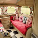 Chic and cute RV interior idea with pink daybed furniture plus decorative LOVE pillows a drawer system black and white tiles floor idea and glass windows plus sweet curtains