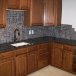 Colorful mosaic backsplash tiles darker stained wood cabinets black countertop white sink and brushed metal faucet
