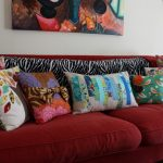 Colorful throw pillows in various sizes and red sofa