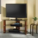 Corner angled TV console with open shelves underneath a small round table some media players