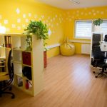 Creative and attractive yellow wall painting idea with white motifs for workspace two sets of working desks with movable chairs  document racks as the partitions wood floors idea a corner yellow Ottoman