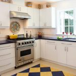 Diamond cut patterned kitchen rug in yellow and dark blue colors  a kitchen set in white theme with white upper and base cabinets black kitchen countertop