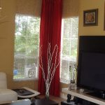 Double corner window curtain idea consisting transparent window shade and bright red window curtain a big flat TV a minimalist TV console white sofas minimalist black table in black staining