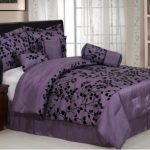 Elegant bedroom decorating idea in purple theme beautiful bedcover and pillow cases with black floral pattern wooden bedside table with storage