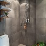 Elegant grey shower space without door with a heldhand shower head and a ceiling showerhead wooden shelves for towels a toilet fixture a small round white table for putting bathing supplies