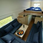 Elevated bed with staircase and storage system U shape sofas in dark blue color scheme and a white coffee table for mobile houses