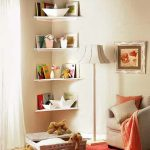 Floating corner book shelves in white and decorative items simple standing lamp reading chair with pillows orange blanket red rug with gold strip a rattan box as the storage of animal stuffs