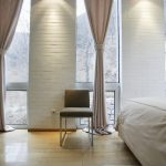 Floor to ceiling curtains idea in soft tone color white bricks wall system a chair a king bed in a modern bedroom