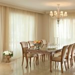 Floor to ceiling white lace curtains for modern dining room a large dining table for eight dining chairs a decorative plant beautiful pendant chandelier white porcelain floors
