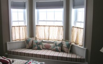 Half way corner window curtain or bay windows with corner bench under windows some throw pillows
