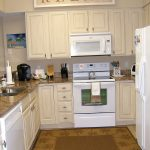 Jute brown kitchen rug in full length size a corner and small kitchen set with cream kitchen cabinets brown granite kitchen counter a deep sink and faucet