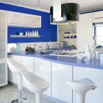 Kitchen plan in blue theme with glossy blue kitchen countertop and kitchen island as bar table as well three white modern barstools L shape storage in white and blurred glass doors a floating shelf