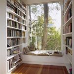 Large bay window with frameless glass window bench with pillows large bookshelves in left and right sides of bay windows