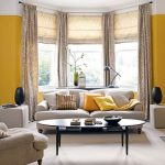 Large Bay Windows With Floor To Ceiling Curtains Yellow Wall Paint A Set Of White Sofa With Multiple Pillows Oval Black Coffee Table White Floors Two Ottoman Furniture Two Decorative Pieces