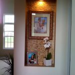 Large wall niche design for organizing picture frames and decorative item with a spot lighting fixture on top