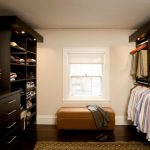 Light fixtures on clothing and shoes closet organizers' top a brown settee furniture a rug for dark staining wood floors